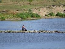 人开会,享有生活的渔在华沙维斯瓦河银行 库存图片