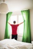 年轻人开窗口帷幕早晨在他的屋子里 库存图片