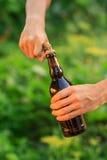 年轻人开头瓶与老开启者的啤酒 图库摄影