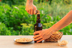 年轻人开头瓶与老开启者的啤酒 免版税库存照片