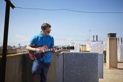 年轻人弹在屋顶大阳台的吉他 库存图片