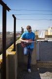 年轻人弹在屋顶大阳台的电吉他 免版税图库摄影