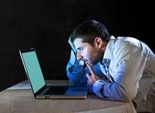 年轻人强调了商人工作夜间在有计算机膝上型计算机的书桌上 库存图片