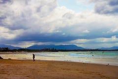 人归成一类-疲乏或哀伤-走在从海浪出来的海滩在与海滩的金黄小时到处都是人和mountians和风暴 库存照片