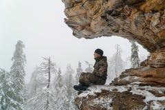 人徒步旅行者坐在放松姿势、冬天山和冷杉森林的思考的风景岩石盖用雪在 库存图片