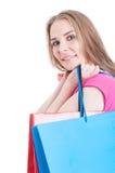 年轻人微笑的女性举行的购物或当前袋子画象  免版税库存照片