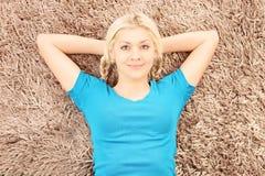 年轻人微笑的女性说谎在地毯 库存图片
