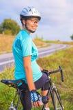 年轻人微笑的愉快的女性白种人骑自行车者运动员画象  免版税库存照片