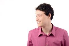 年轻人微笑的看对边。 免版税库存图片