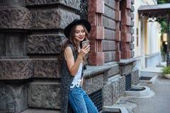 年轻人微笑的美丽的深色的女孩听与耳机的音乐户外 免版税图库摄影