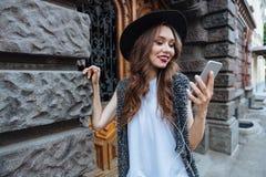 年轻人微笑的美丽的深色的女孩听与耳机的音乐户外 图库摄影