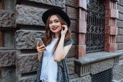 年轻人微笑的美丽的深色的女孩听与耳机的音乐户外 免版税库存照片