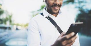 年轻人微笑的非洲人画象使用智能手机手的,当站立在晴朗的城市街道时 概念的愉快 免版税图库摄影