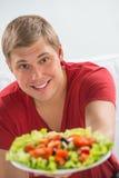 年轻人微笑的食人的素食沙拉 图库摄影