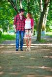 年轻人怀孕的夫妇走的春天公园 免版税库存图片