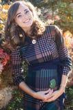 年轻人怀孕的微笑的妇女在秋天公园 图库摄影