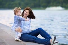 年轻人怀孕的母亲和她的小放松在a的小女儿 免版税库存图片