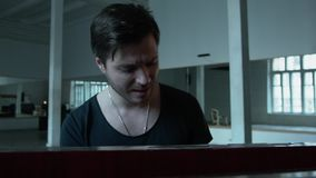 年轻人情感地唱歌在钢琴 一件T恤杉的性感的人有大切开的和有在他的附近的一个链子的 影视素材