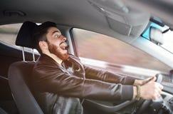 年轻人惊吓了在汽车的轮子 图库摄影