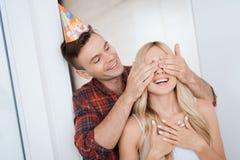 人惊奇为女孩` s生日做准备 他用人工闭上了她的眼睛 人微笑并且带领女孩a 免版税库存图片