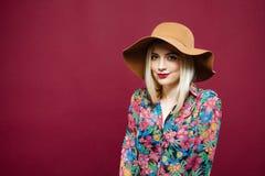 令人惊讶的金发碧眼的女人秀丽画象摆在桃红色背景的帽子和五颜六色的衬衣的 演播室短逗人喜爱的少妇 库存图片