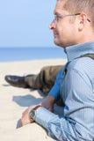人成熟在的沙子海放松 免版税库存照片