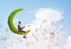 人或学生坐绿色月亮和阅读书 免版税库存图片