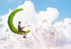 人或学生坐绿色月亮和阅读书 库存图片