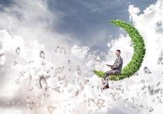 人或学生坐绿色月亮和阅读书 免版税图库摄影