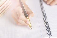 人或少年在一个方格的笔记本写一支黑黄色笔 免版税库存照片