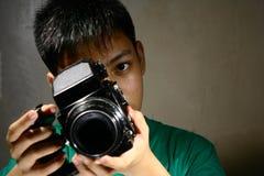 人或青少年看通过一台中等格式影片照相机 库存图片
