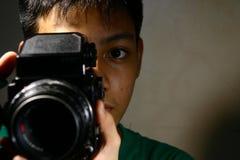 人或青少年看通过一台中等格式影片照相机 免版税库存照片