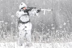 人战士在狩猎的冬天与在瞄准在雪的白色冬天伪装的狙击步枪身分 库存图片