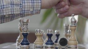 人手制定棋子 两个人震动移交棋盘 与银色插入物的美好的国际象棋棋局 股票录像