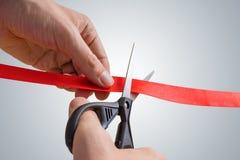 人手剪彩与剪刀的红色 开幕活动 免版税图库摄影