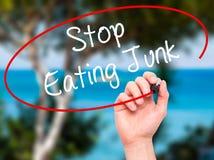 人手吃与黑标志的文字中止破烂物在视觉sc 免版税图库摄影