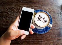 人手在咖啡店的用途智能手机 免版税图库摄影