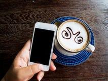 人手在咖啡店的用途智能手机 图库摄影