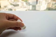 人手在嘲笑的用途橡皮擦差错撤除的纸板料 免版税库存照片