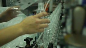 人手在矿泉水,碳酸化合的柠檬水的传动机生产投入瓶 影视素材