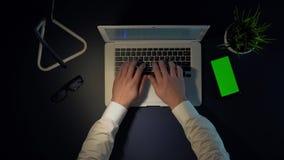 人手在膝上型计算机键盘键入,当坐在桌上在晚上时 股票视频