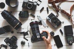 人手在透镜和辅助部件旁边拿着在表上的数字照相机在白色木背景 顶视图 免版税库存图片