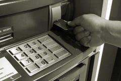 人手对黑白的自动出纳机ATM的插入物卡片 免版税库存图片