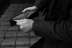 人手开放检查的空的钱包发生了现金 免版税库存照片