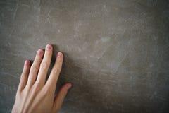 年轻人手感人的混凝土墙 库存图片