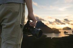 人手拿着一座照相机、海和山与日出后面 图库摄影