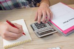 人手的关闭使用计算器和文字做笔记与在家计算关于费用办公室 免版税图库摄影