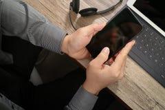 人手顶视图使用VOIP耳机的有数字式片剂comp的 库存图片