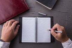人手顶视图写在有笔的空的笔记本的在办公室 免版税库存照片