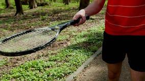 人打从球拍的网球 r 打网球的年轻人 在一件红色T恤杉打扮的人和 股票录像